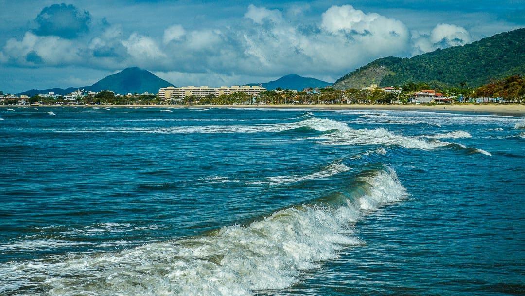 Ondas quebrando na Praia do Cruzeiro ou de Iperoig, com imóveis na orla da Praia do Itaguá ao fundo