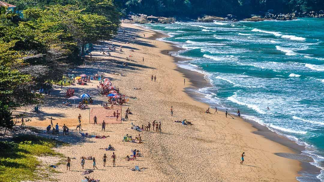 Banhistas na areia em um final de tarde ensolarado de domingo com altas ondas rolando no mar da Praia Vermelha do Centro