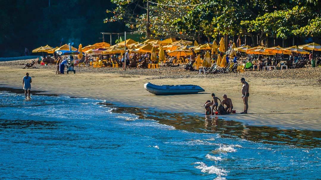Famílias se divertindo nas areias da Praia da Almada e, ao fundo, inúmeras cadeiras com guarda sóis dos poucos e bons quiosques do local
