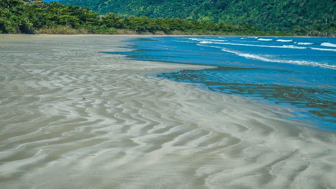 Areias escuras e compactas da Praia da Fazenda, meca do Ecoturismo em Ubatuba e uma das praias mais extensas da cidade
