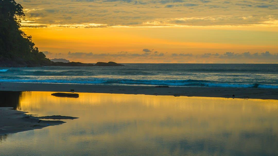 Reflexo dos primeiros raios de sol no rio que deságua no extremo esquerdo da Praia de Itamambuca