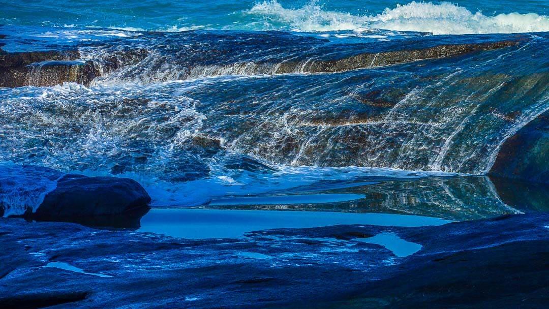 Ondas deslizando pelas rochas na costeira da Praia das Conchas em Ubatuba