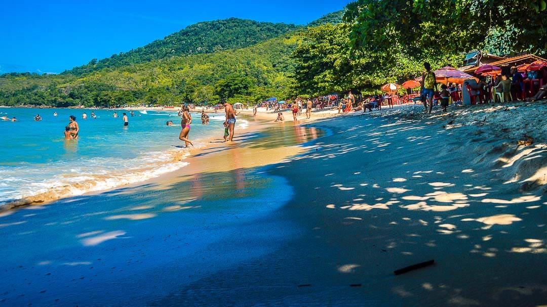 Crianças e adultos se divertem em um dia ensolarado na Praia da Caçandoca, ótima praia de Ubatuba para passar o dia com a família