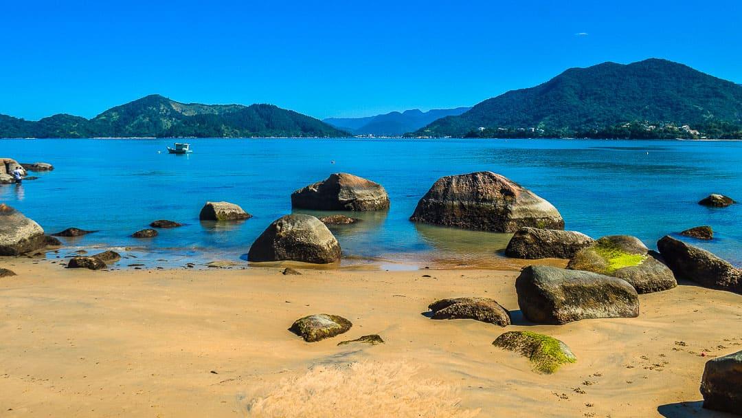 Ao fundo a região do Saco da Ribeira e, na orla da Prainha da Enseada, rochas se distribuem pela areia