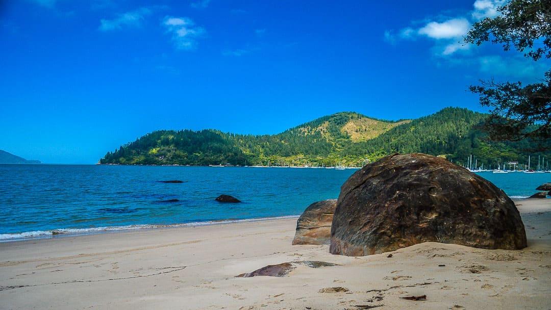 Formações rochosas no centro da Praia do Lamberto e, ao fundo, as praias acessíveis pela Trilha das 7 Fontes