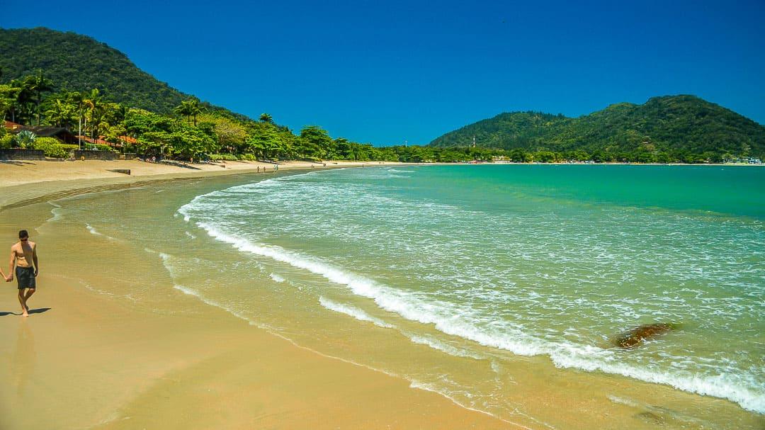 Sem turistas na baixa temporada, a ampla extensão da Praia do Lázaro se revela, assim como as grandes sombras das árvores na orla
