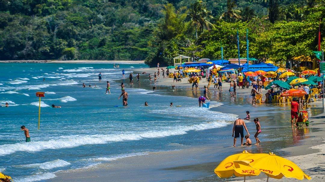 Centenas de pessoas aproveitando um dia ensolarado na orla da Praia de Maranduba, uma das mais movimentadas e badaladas da cidade