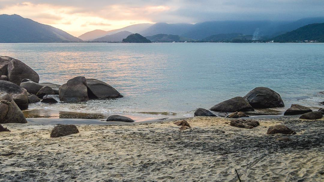 Areias escuras e rochas na orla com o pôr do sol ao fundo na Praia do Oeste em Ubatuba