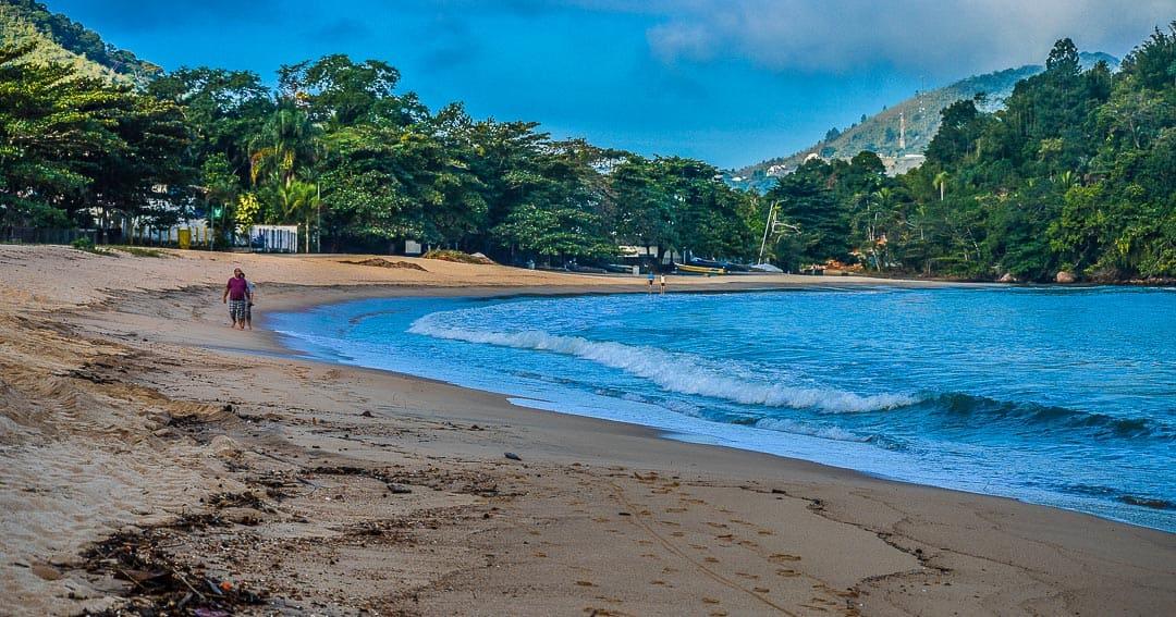 Pessoas caminhando na orla da Praia do Perequê-Mirim, uma ótima opção do que fazer, já que é costumeiramente classificada como uma praia imprópria de Ubatuba