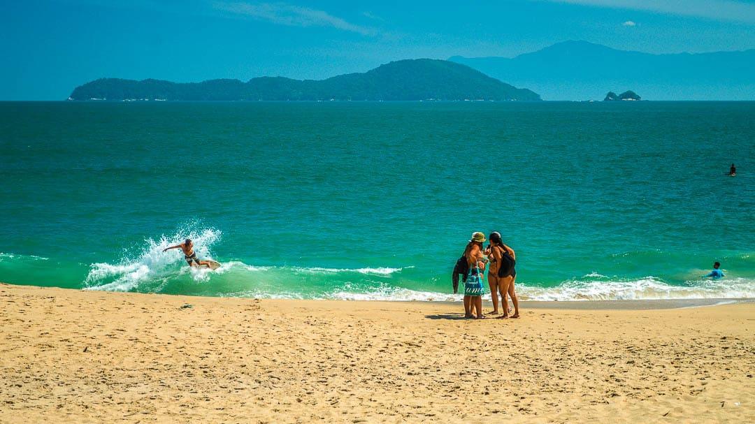 Mulheres conferindo fotos no celular e jovens pegando ondas de skimboard na Praia da Sununga em Ubatuba