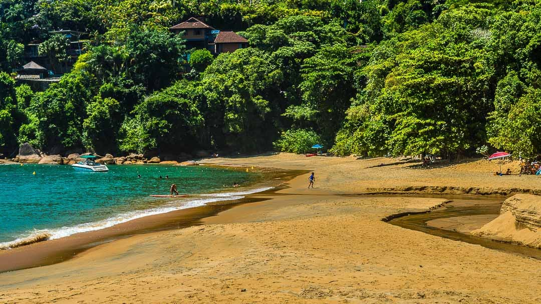 Criança brincando na areia e homem entrando no mar com prancha de stand up paddle na Praia Vermelha do Sul, excelente para banho e ótima para ir com a família