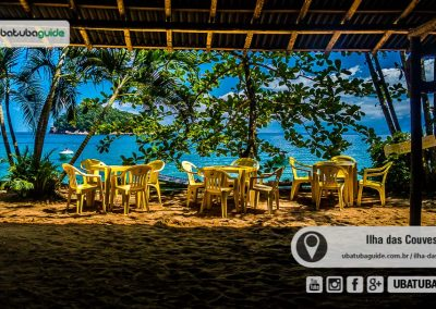 Cadeiras e mesas de plástico com bela vista da Praia de Terra na Ilha das Couves como pano de fundo