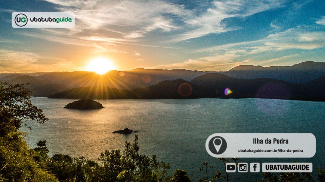 Últimos raios de sol se esvaindo pelas curvas da Serra do Mar ao fundo, com destaque para a Ilha da Pedra na parte inferior da imagem