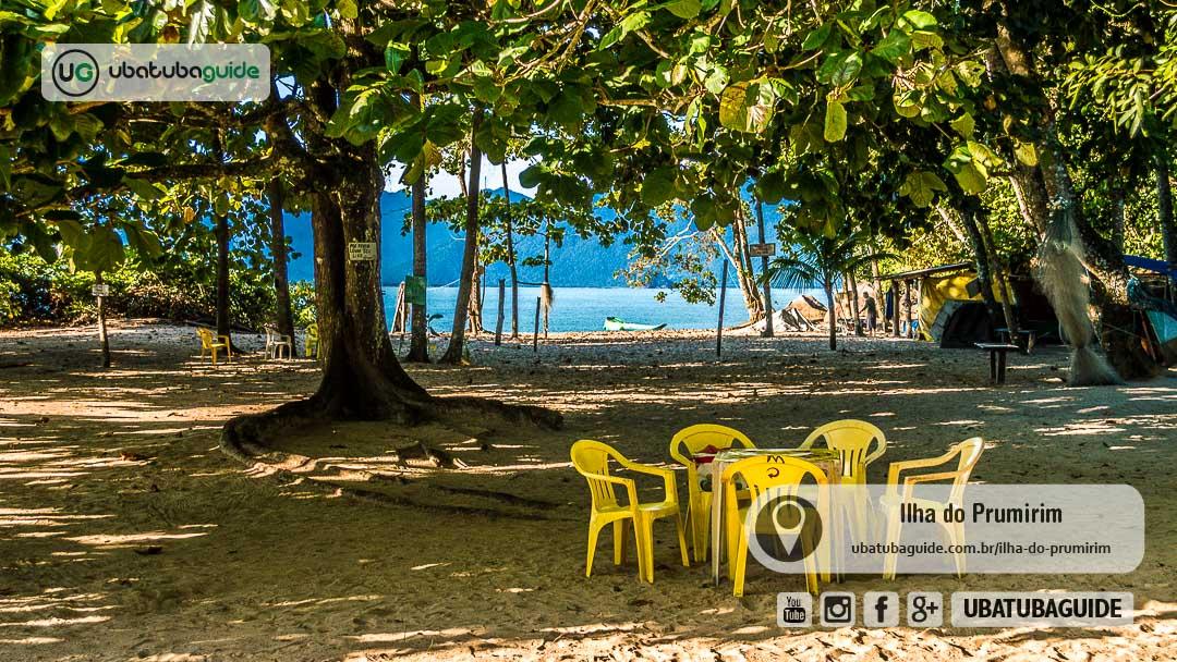 Cadeiras e mesas na área sombreada, onde fica o único quiosque da Ilha do Prumirim