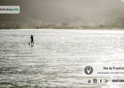 Com a Praia do Prumirim ao fundo, pessoa retorna remando de stand up paddle da Ilha do Prumirim no final de tarde. Uma das maneiras de ir para a ilha.