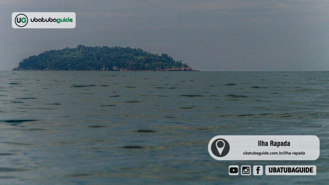 Registro da Ilha Rapada distante no horizonte durante passeio de lancha