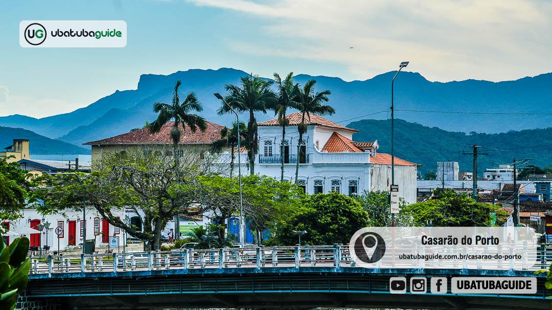 Fachada do Casarão do Porto de Ubatuba parcialmente oculta sob árvores nas margens do Rio Grande, que passa sob a ponte Félix Guisard que conecta o centro ao Perequê-Açú com o Pico do Corcovado imponente ao fundo na Serra do Mar