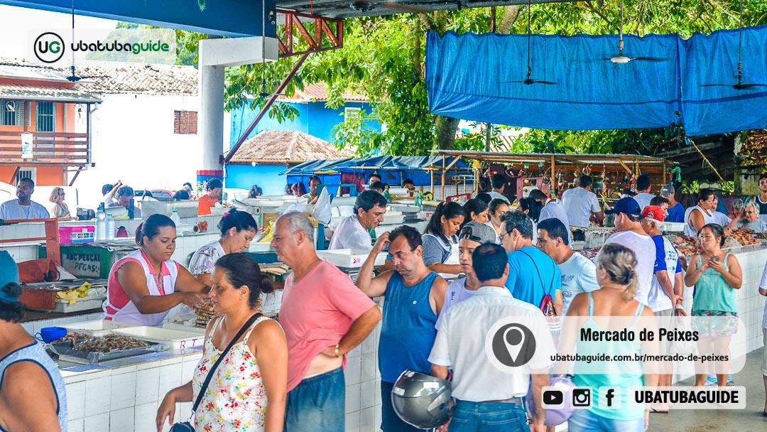 Dezenas de pessoas visitando o Mercado Municipal de Pescados de Ubatuba com inúmeros pescadores realizando atendimento nos balcões do Mercado de Peixes, como é popularmente conhecido