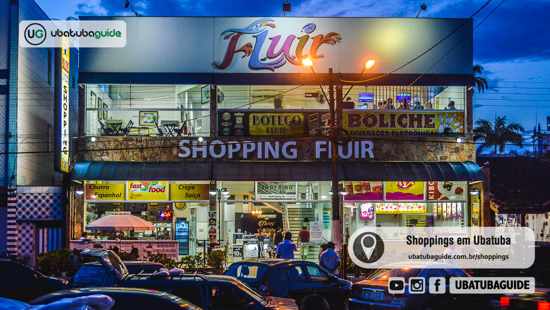Fachada do Shopping Fluir no início do entardecer com lojas iluminadas. Ele é um dos poucos shoppings em Ubatuba.