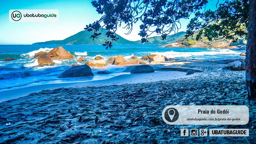 Ilha Anchieta no plano de fundo, com rochas na orla e na água da Praia do Godói, a última acessível pela Trilha da Ponta da Espia