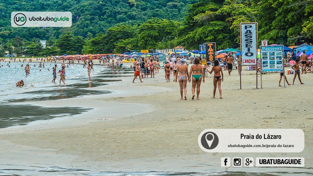 Centenas de turistas caminhando e se banhando na Praia do Lázaro diante de placas indicando a oferta de passeio de lancha em Ubatuba